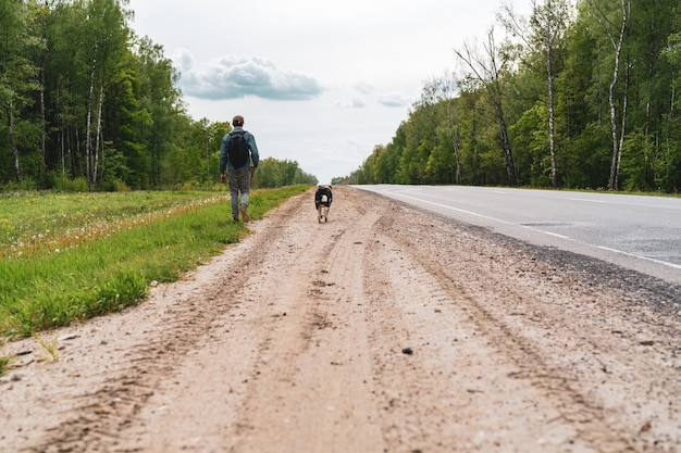 Young man, a teenager with a dog is walking on the side of the road