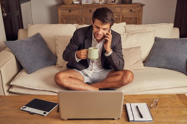 화상 회의에서 집에서 재택 근무하는 젊은이, 양복과 반바지에 소파에 앉아. 커피를 마시고 휴대 전화로 이야기하십시오.