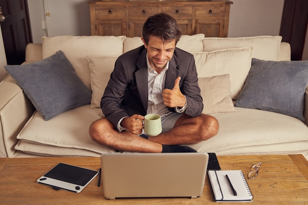 Young man teleworking from home in video conference, sitting on the couch in a suit and shorts. he drinks coffee and makes a sign of like with his hand.