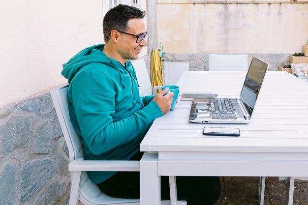 Молодой человек удаленно работает со своим ноутбуком, печатая на клавиатуре, в саду своего дома