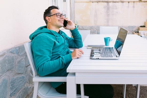 Молодой человек удаленно работает со своим ноутбуком, пишет в блокноте и разговаривает по мобильному телефону в саду своего дома
