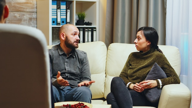 Young man telling his wife in front of therapist about what makes him unhappy regarding their relationship.