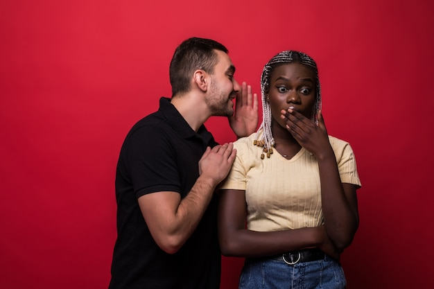 Young man telling a secret to african woman over a red background