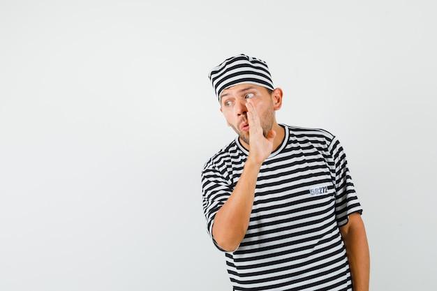 縞模様のtシャツ、帽子で手の後ろに秘密を語る若い男。