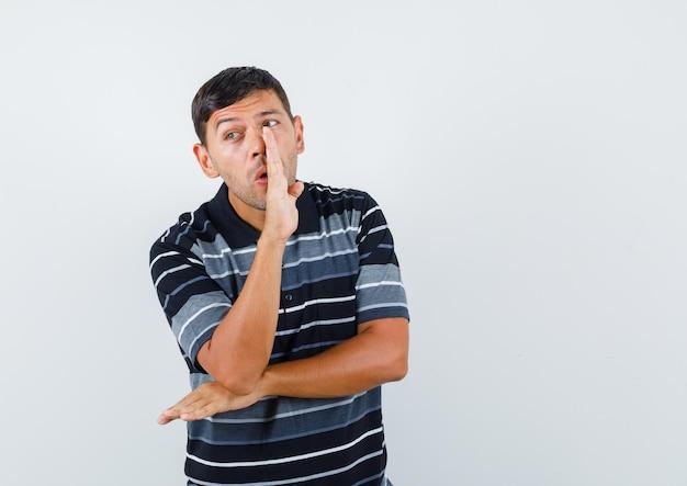 T-셔츠 전면 보기에 손 뒤에 비밀을 말하는 젊은 남자.