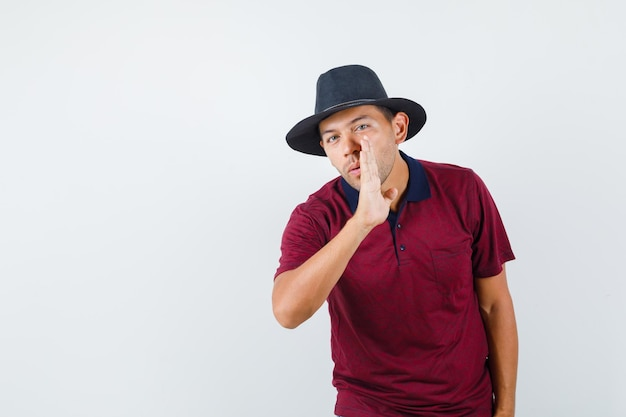 Young man telling secret behind hand in t-shirt, hat and looking curious , front view.
