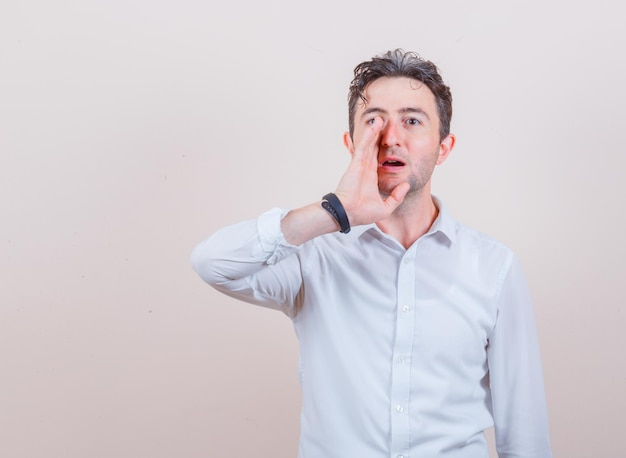 Young man telling secret with hand near mouth in white shirt