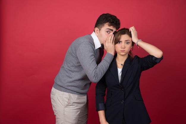 若い男は赤い壁で彼のガールフレンドにいくつかのニュースを伝えます