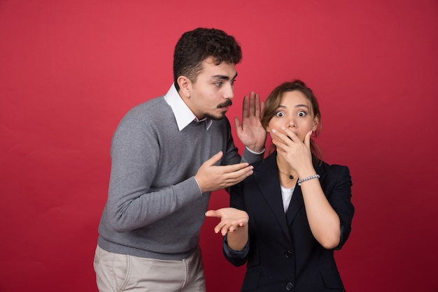 젊은 남자가 붉은 벽에 여자 친구에게 몇 가지 소문을 전합니다.