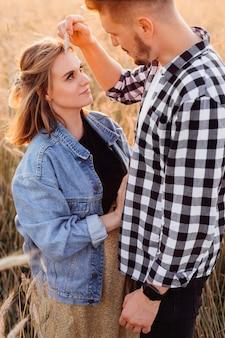 Молодой человек нежно проводит колосом по лицу своей беременной жены, которая смотрит на него с любовью и доверием. беременность и уход. забота и внимание. любовь и надежда. образ жизни. прогулки на природе.