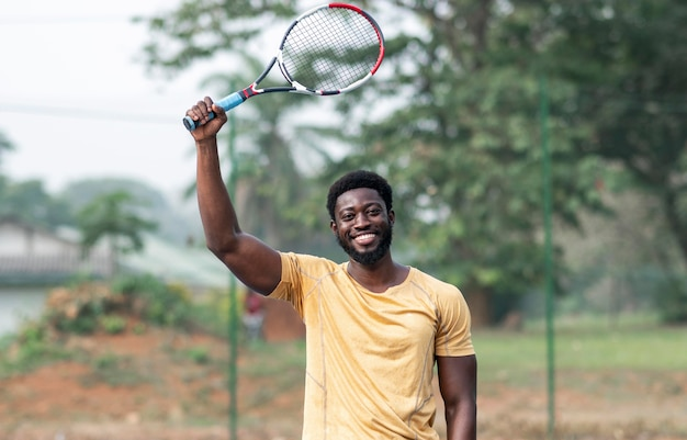 Giovane uomo sul campo da tennis giocando
