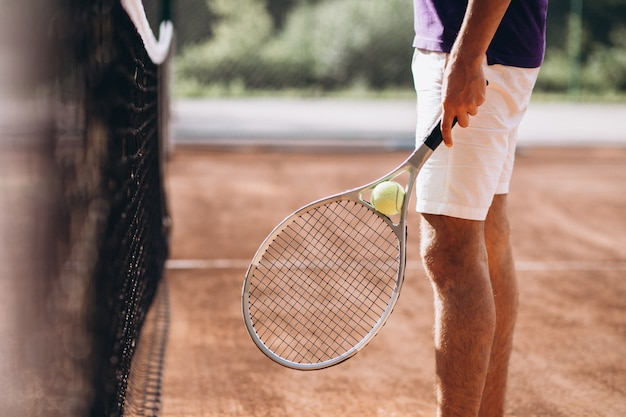 Young man tennis player at the court, tennis racket close up