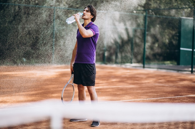 Young man tennis player at the court