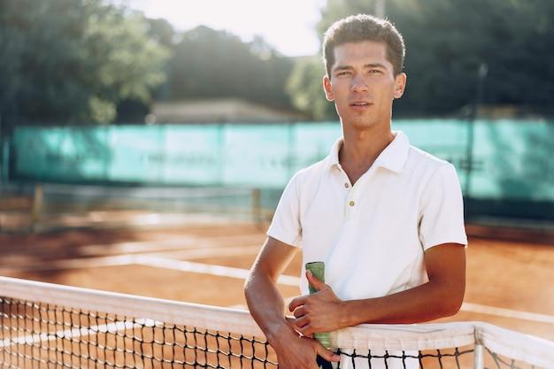 Молодой человек теннисист с ракеткой стоит на теннисном корте