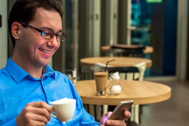 若い男は、カフェでメッセージを送る。テーブルでスマートフォンで笑顔と文字通りの幸せなビジネスマン