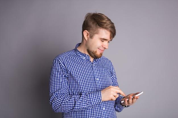 Текстовые сообщения молодого человека на умном телефоне изолированном на серой стене. улыбающийся парень держит смартфон
