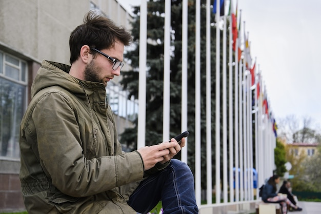 Young man texting in a mobile phone sitting on a bench in the square
