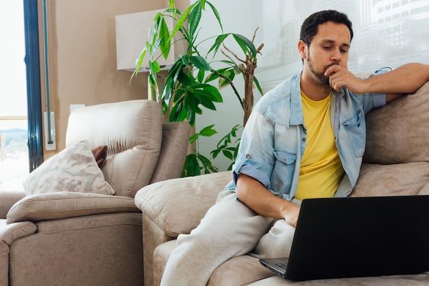 Молодой человек думает о чем-то дома на своем диване и смотрит в ноутбук
