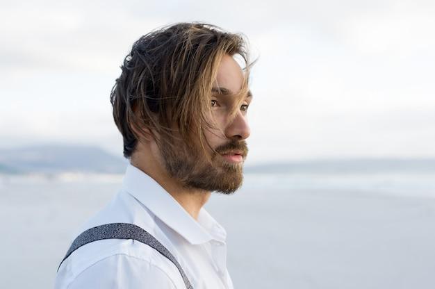 ビーチで考えている若い男