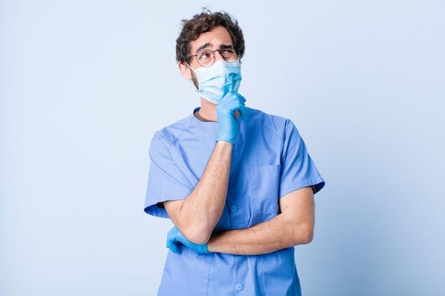 若い男が考えて、疑わしくて混乱していて、さまざまな選択肢があり、どの決断をするべきか迷っています。コロナウイルスの概念