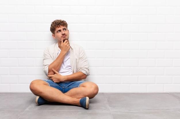 若い男は考え、疑わしくて混乱し、さまざまな選択肢を持って、どの決定を下すか疑問に思っています