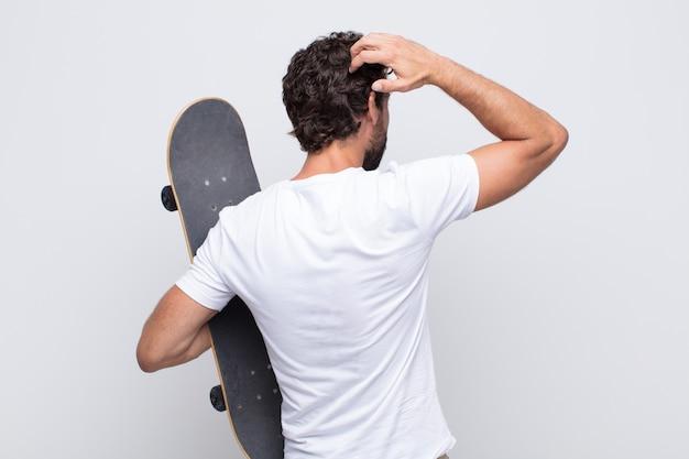 젊은 남자가 생각하거나 의심하고, 머리를 긁적이며, 의아해하고 혼란스러워하는 느낌, 뒤로 또는 후면보기