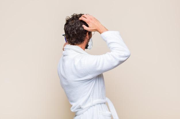 젊은 남자가 생각하거나 의심하고, 머리를 긁적이며, 의아해하고 혼란스러워합니다.