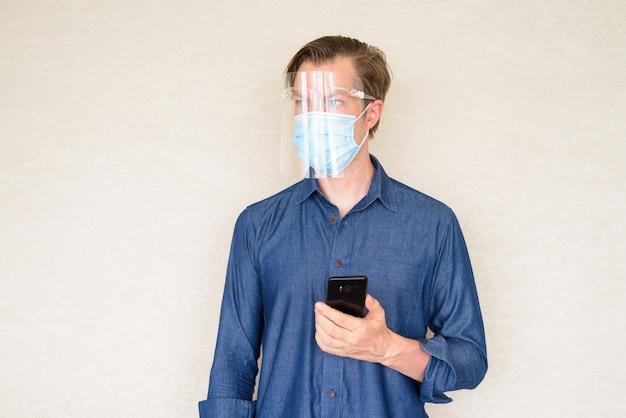 Молодой человек думает, используя телефон с маской и щитком для лица на бетонной стене