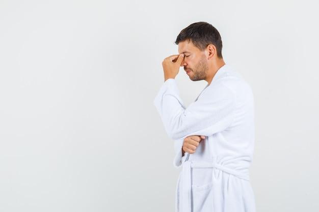 Молодой человек думает с закрытыми глазами в белом халате.