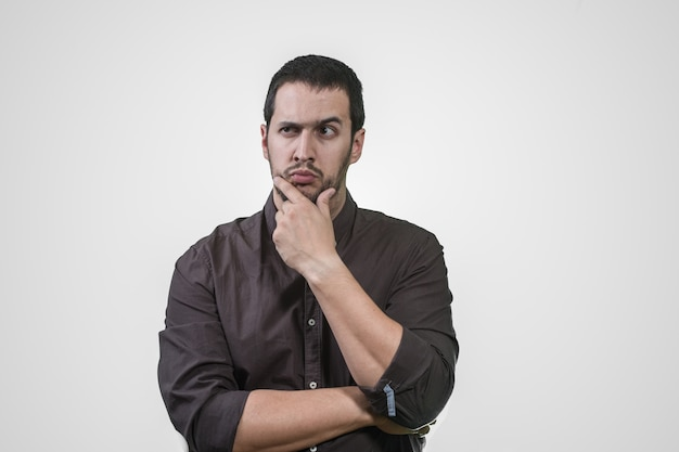 Young man thinking with his hand on his face and shirt