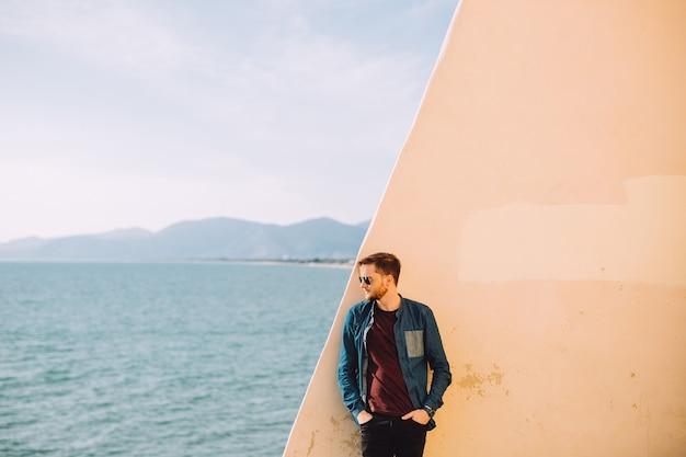 그의 뒤에있는 삶에 대해 생각하는 청년은 바다와 산을 본다