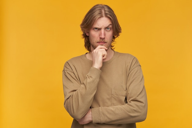 Молодой человек, задумчивый парень со светлыми волосами, бородой и усами. в бежевом свитере. касается его подбородка и приподнимает бровь. изолированные над желтой стеной