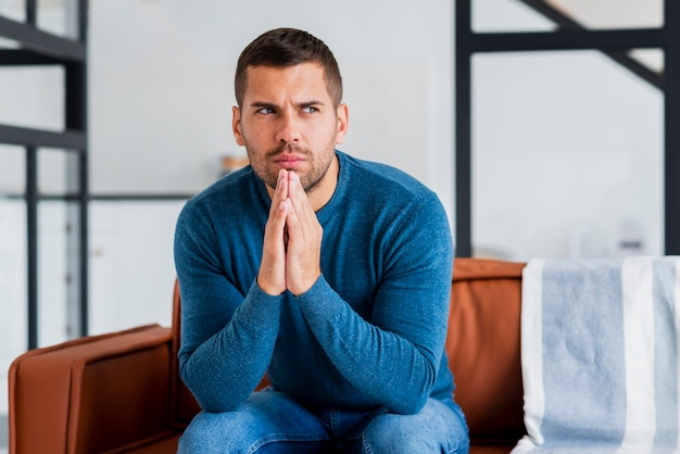 Young man on thoughts while sitting on couch