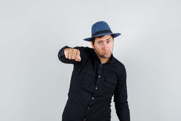 Молодой человек угрожает кулаком в черной рубашке