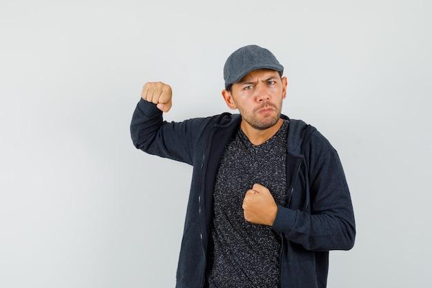 T- 셔츠, 재킷, 모자에 주먹으로 위협하고 화가 찾고 젊은 남자