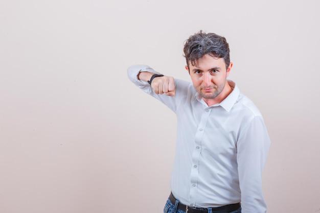 젊은 남자가 흰 셔츠, 청바지에 주먹으로 위협하고 자신감을 찾고
