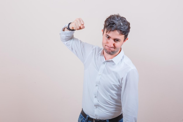 Giovane che minaccia di pugno in camicia bianca, jeans e sembra nervoso