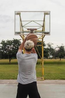 放棄されたバスケットボールコートのフープにボールを投げる若い男。