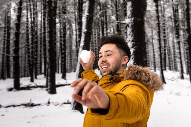 雪に覆われた森に雪玉を投げる若い男