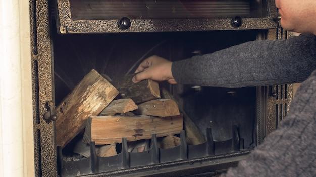 Молодой человек бросает бревна в открытый камин в доме