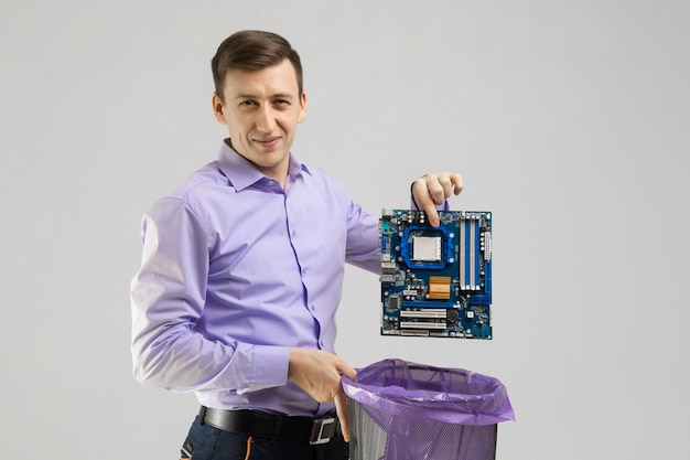 Young man throws motherboard in trash isolated on light background