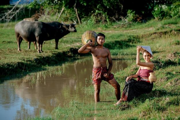 沼の近くに座っている美しい女性と料理のためのcatgh魚に竹釣りトラップを立って保持しているトップレスの若い男