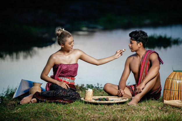 Young man topless wearing loinclothes in rural lifestyle and young pretty woman, farmer couple has dinner