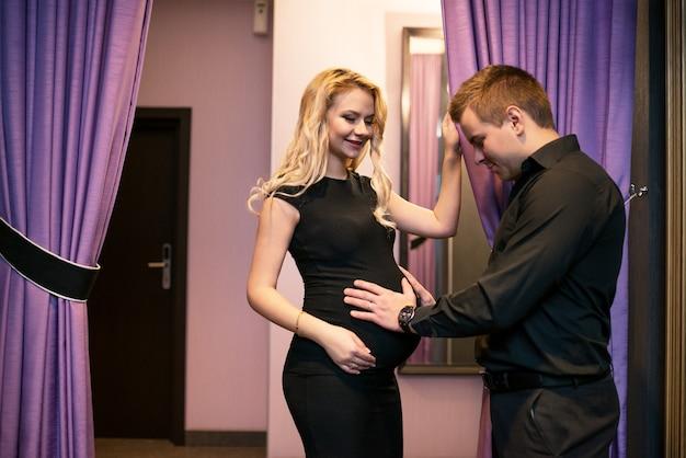 젊은 남자가 그의 아름다운 임신 한 아내의 배를 만지고 가족의 보충을 즐길 수 있습니다.