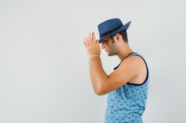 青い一重項の指で帽子に触れてハンサムに見える若い男。 。