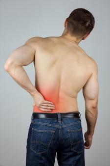 若い男が痛みのために背中に触れる