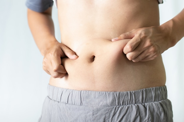 Young man touching his fat belly. fat and health concept