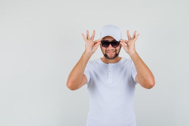 T- 셔츠, 모자에 웃 고 메리 찾고있는 동안 그의 안경을 만지고 젊은 남자. 전면보기.
