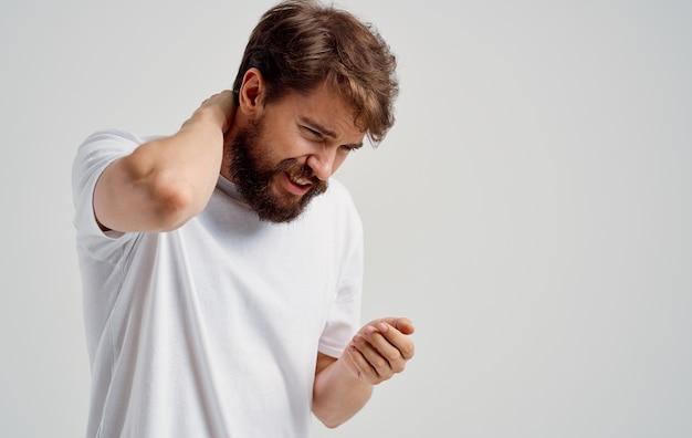 若い男が手で首に触れる脊椎の痛みの側面図