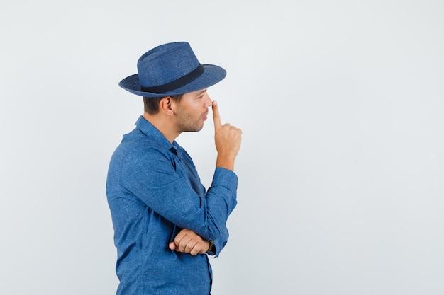 Молодой человек трогает нос пальцем в голубой рубашке, шляпе и смотрит задумчиво.